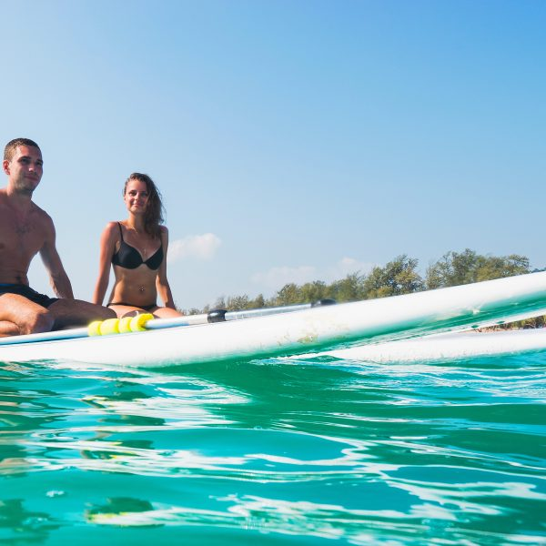Couple Sitting Paddle Surfing . Beautiful Tropical Ocean, Active Beach Lifestyle.