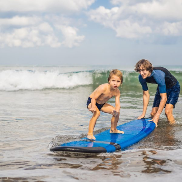 Father or instructor teaching his 4 year old son how to surf in the sea on vacation or holiday. Travel and sports with children concept. Surfing lesson for kids.