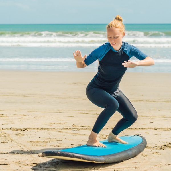 Young woman is training to stand on the surf before the first surfing lesson.