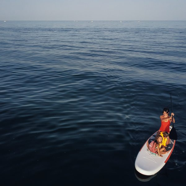 Mother with two daughters stand up on a paddle board. At sea, calm.