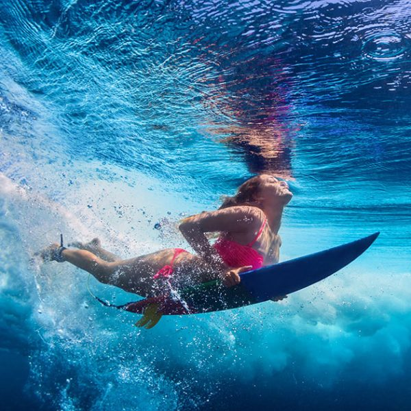 Young active girl wearing bikini in action - surfer with surf bo